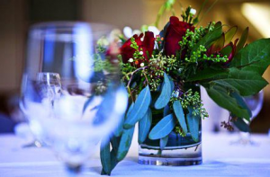 Blurred empty wine glass with focus on roses centerpiece
